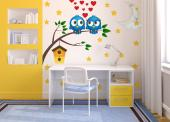 Wall decals for a nursery or kids room. The night has come and two chubby blue owls come out of their wooden birdhouse and sit on a tree branch. They're deeply in love and hearts take form above their heads. Watching the couple are the Moon and its pet cloud and many, many stars...